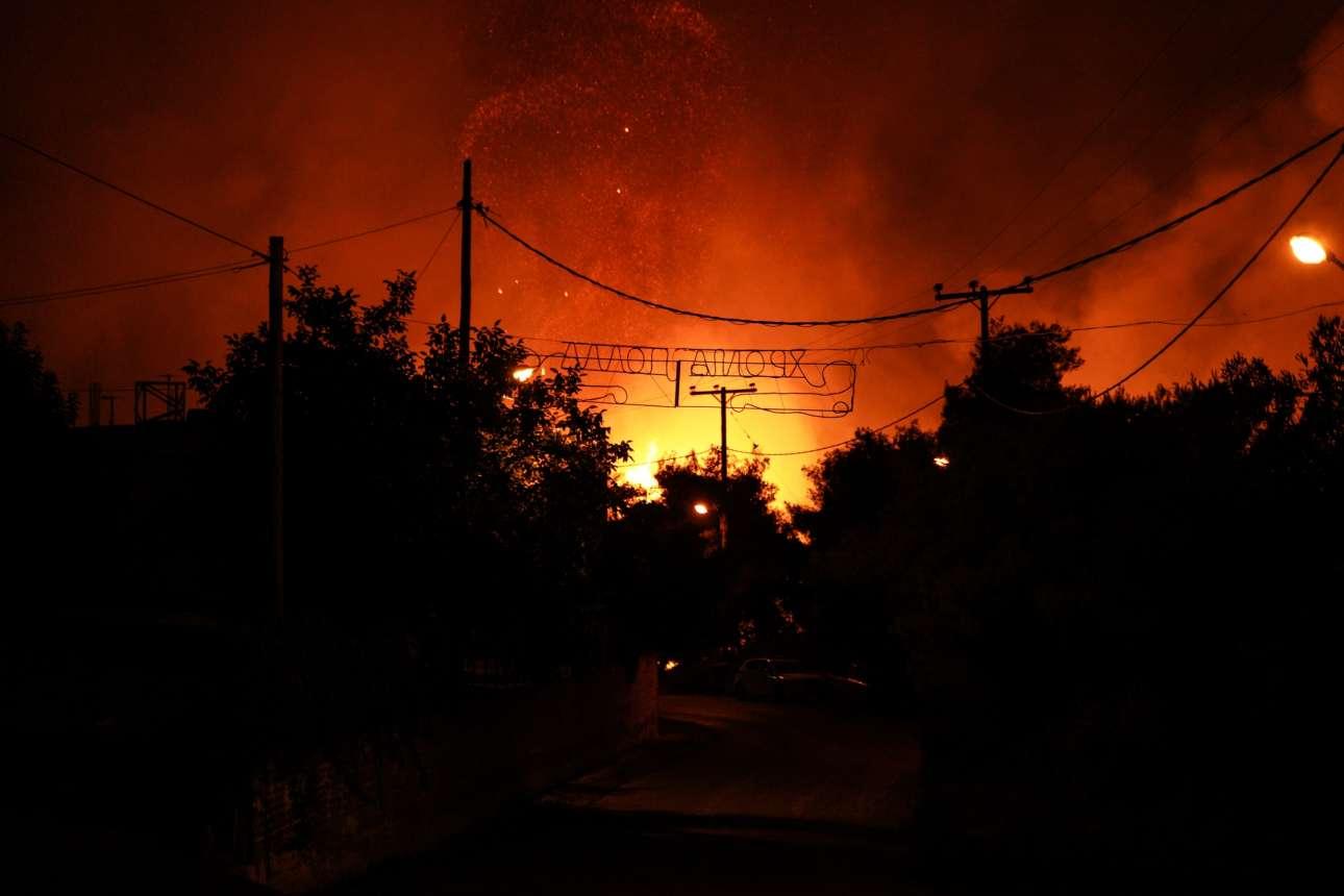 Ειρωνεία. Το (μόνιμο) φωτεινό σήμα με ευχές για χρόνια πολλά διακρίνεται μέσα από το απόκοσμο φως της πυρκαγιάς στη Μακρυμάλλη