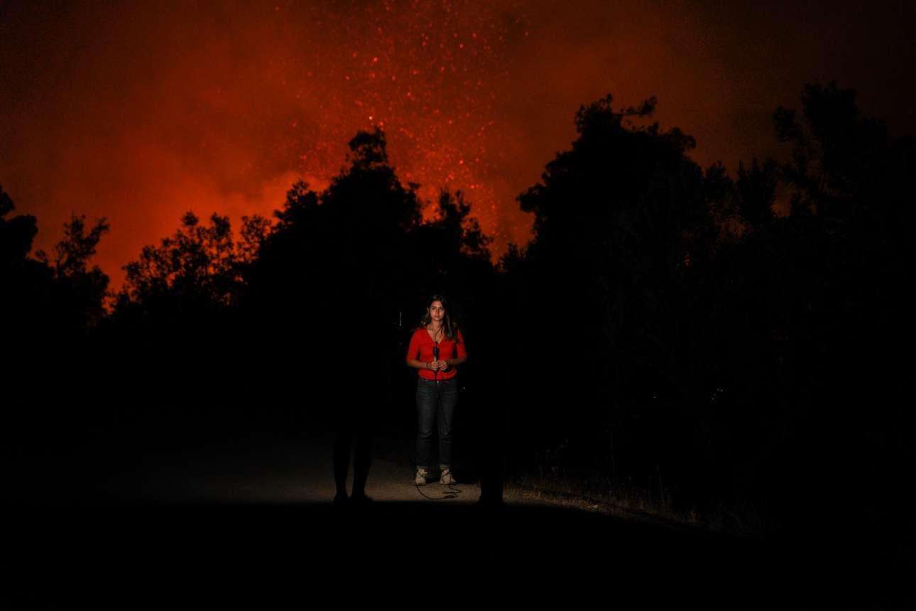 Νεαρή τηλεοπτική ρεπόρτερ επί το έργον, με φόντο το κόκκινο από τις φλόγες