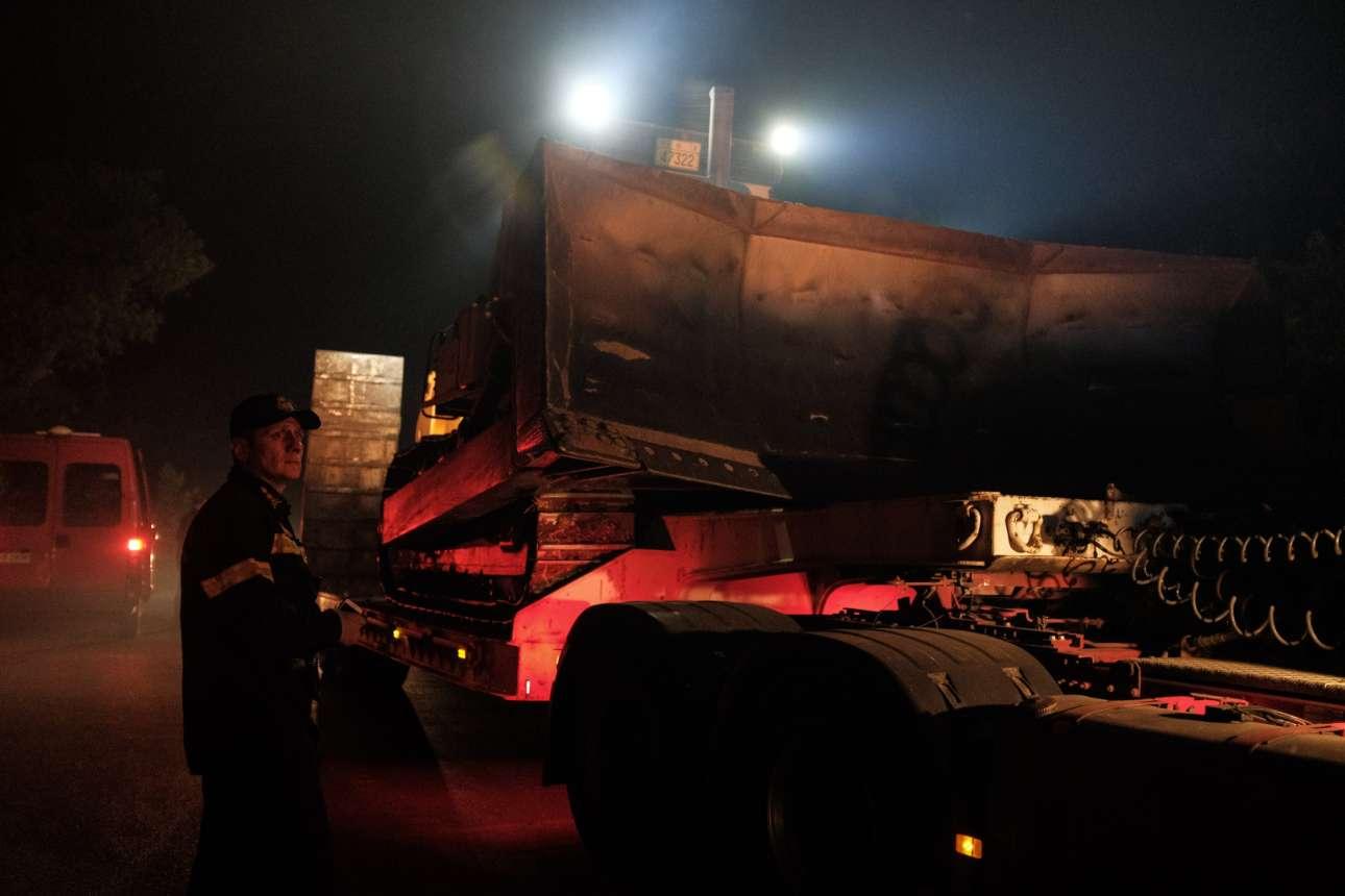 Ανδρας της Πυροσβεστικής μπροστά σε ένα βαρύ όχημα που μεταφέρει εκσκαφείς. Η μάχη τη νύχτα δόθηκε για τη δημιουργία αντιπυρικών ζωνών