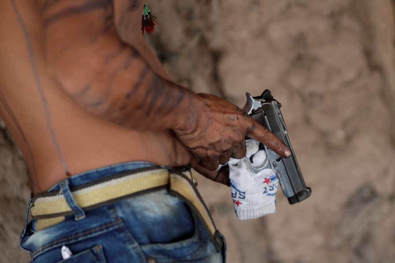 Ενας Γκουαχαχάρα κρατά στο ένα χέρι το πιστόλι καθώς ετοιμάζεται για περιπολία την περιοχή και στο άλλο μια κάλτσα με την οποία καθαρίζει τη σκανδάλη.