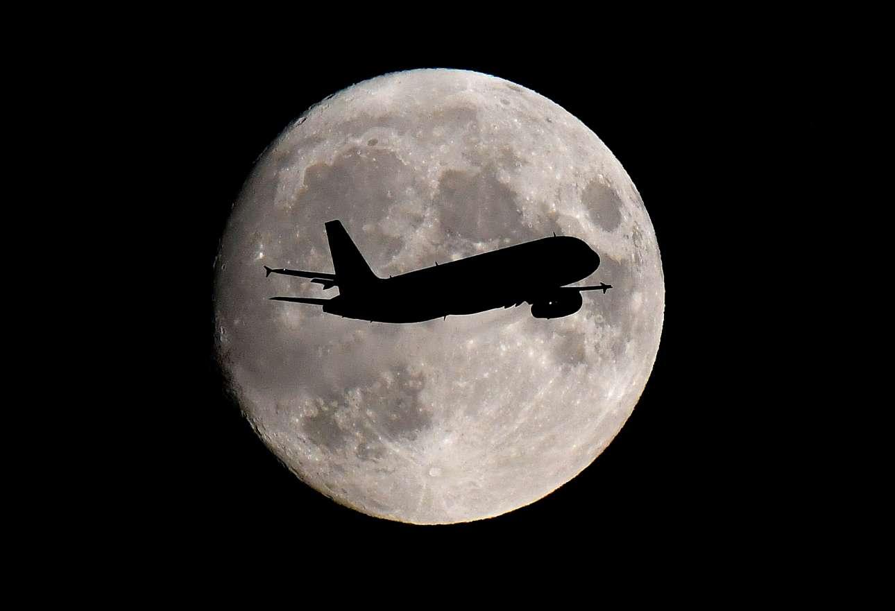 Επιβατικό αεροπλάνο περνά ακριβώς μπροστά από το μαγευτικό φεγγάρι καθώς προσγειώνεται στο αεροδρόμιο του Χίθροου στο Λονδίνο