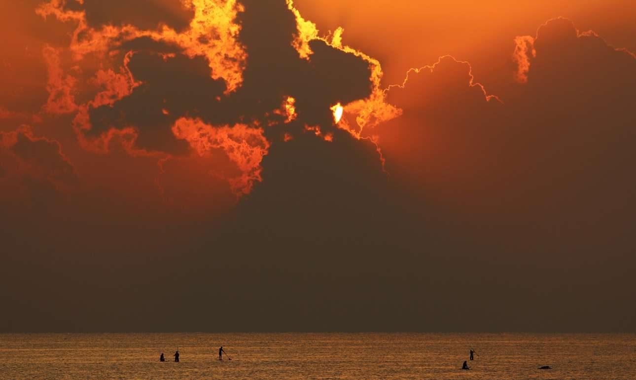 Ο ήλιος ανατέλλει γεμίζοντας με χρώματα τον ουρανό σε παραλία της Λάρνακας