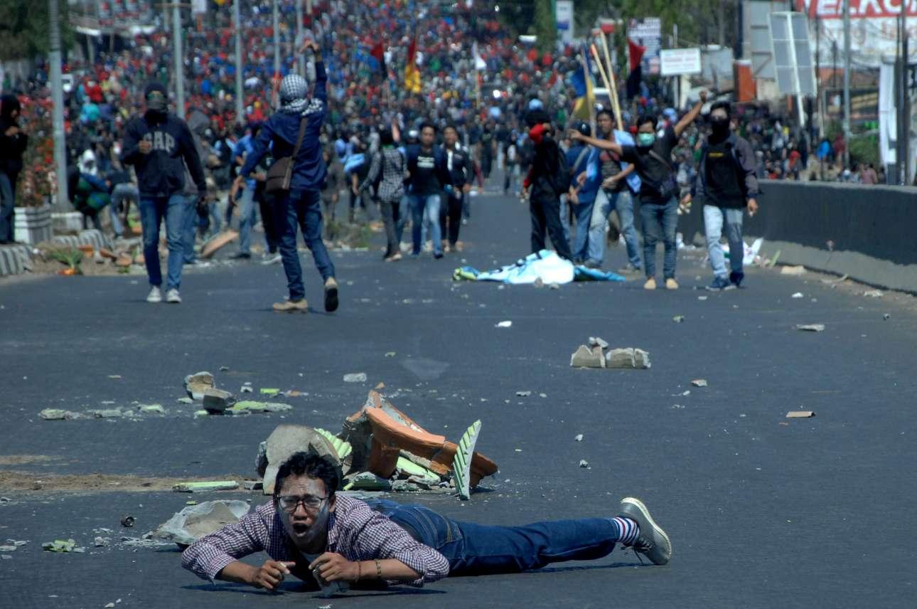 Ανδρας στη Μακάσαρ της Ινδονησίας έχει πέσει στο έδαφος τη στιγμή που πίσω του συγκρούονται φοιτητές με τις δυνάμεις ασφαλείας