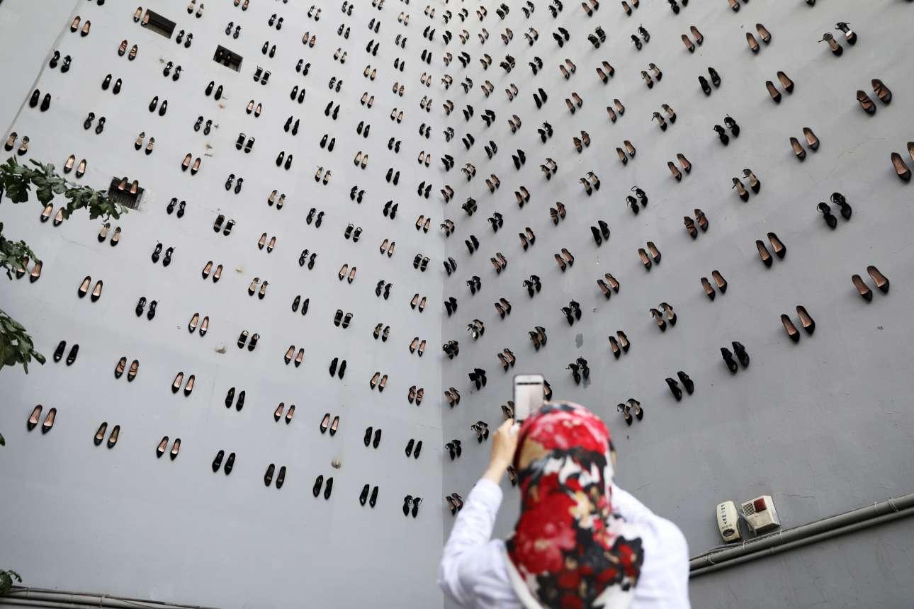 Γυναίκα φωτογραφίζει την πρόσοψη κτηρίου στην Κωνσταντινούπολη γεμάτη με 440 ζευγάρια γόβες. Η εγκατάσταση του εικαστικού Vahit Tuna τιμά τις 440 γυναίκες που πέθαναν το 2018 στην Τουρκία από ενδοοικογενειακή βία