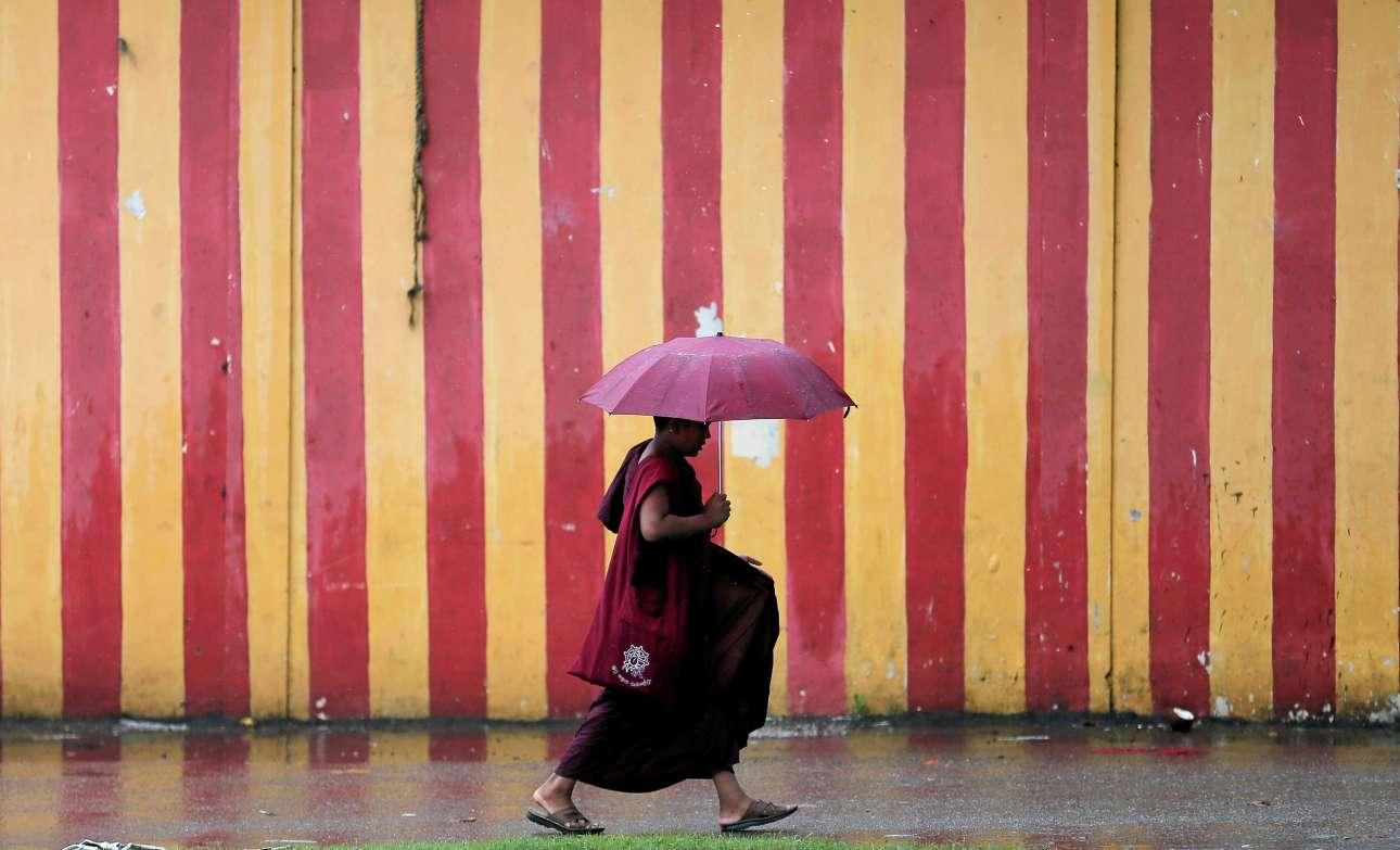 Και οι βουδιστές βρέχονται. Ενας βιαστικός μοναχός περπατάει στη βροχή στο Κολόμπο της Σρι Λάνκα