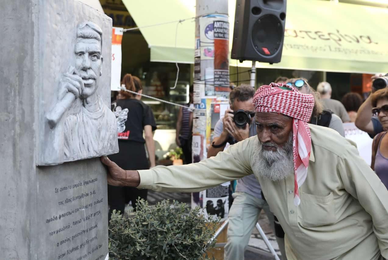 Ιστορική φωτογραφία από τον Πειραιά και τις εκδηλώσεις στη μνήμη του Παύλου Φύσσα. Ο πατέρας του Σαχζάτ Λουκμάν (που δολοφονήθηκε από μέλη της Χρυσής Αυγής) «σπάει» τις ισλαμικές απαγορεύσεις και αγγίζει τον «πέτρινο» Παύλο Φύσσα. Οι μουσουλμάνοι απαγορεύεται να αγγίζουν αγάλματα, ανδριάντες, εικαστικές μορφές προσώπων κάθε είδους αφού αυτό θεωρείται ένδειξη ειδωλολατρικής συμπεριφοράς