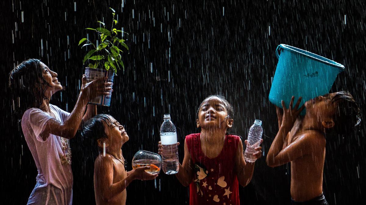 Μία παρέα παιδιών συλλέγει νερό κατά τη διάρκεια έντονης βροχόπτωσης στις Φιλιππίνες. Παρόλο που οι τυφώνες στις Φιλιππίνες είναι συχνοί, οι πολίτες εξακολουθούν να λατρεύουν το ζωογόνο στοιχείο του νερού