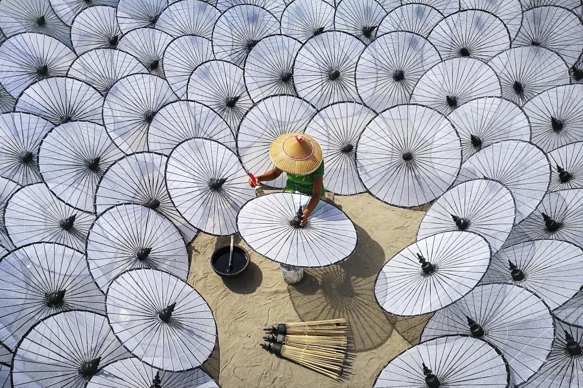 Μία γυναίκα φτιάχνει παραδοσιακές ομπρέλες σε βιοτεχνία, στην πόλη Μανταλέι της Μιανμάρ. Η κατασκευή μιας παραδοσιακής ομπρέλας δεν μπορεί να γίνει από ένα άτομο ή μέσα σε μια μέρα: διαφορετικοί εργαζόμενοι είναι υπεύθυνοι για διαφορετικά μέρη για να μπορέσει να ολοκληρωθεί μια ομπρέλα
