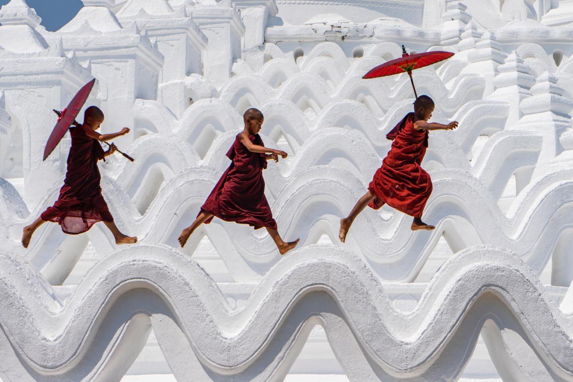 Τρεις νεαροί μοναχοί διασκεδάζουν πάνω στην οροφή παγόδας στη Μιανμάρ