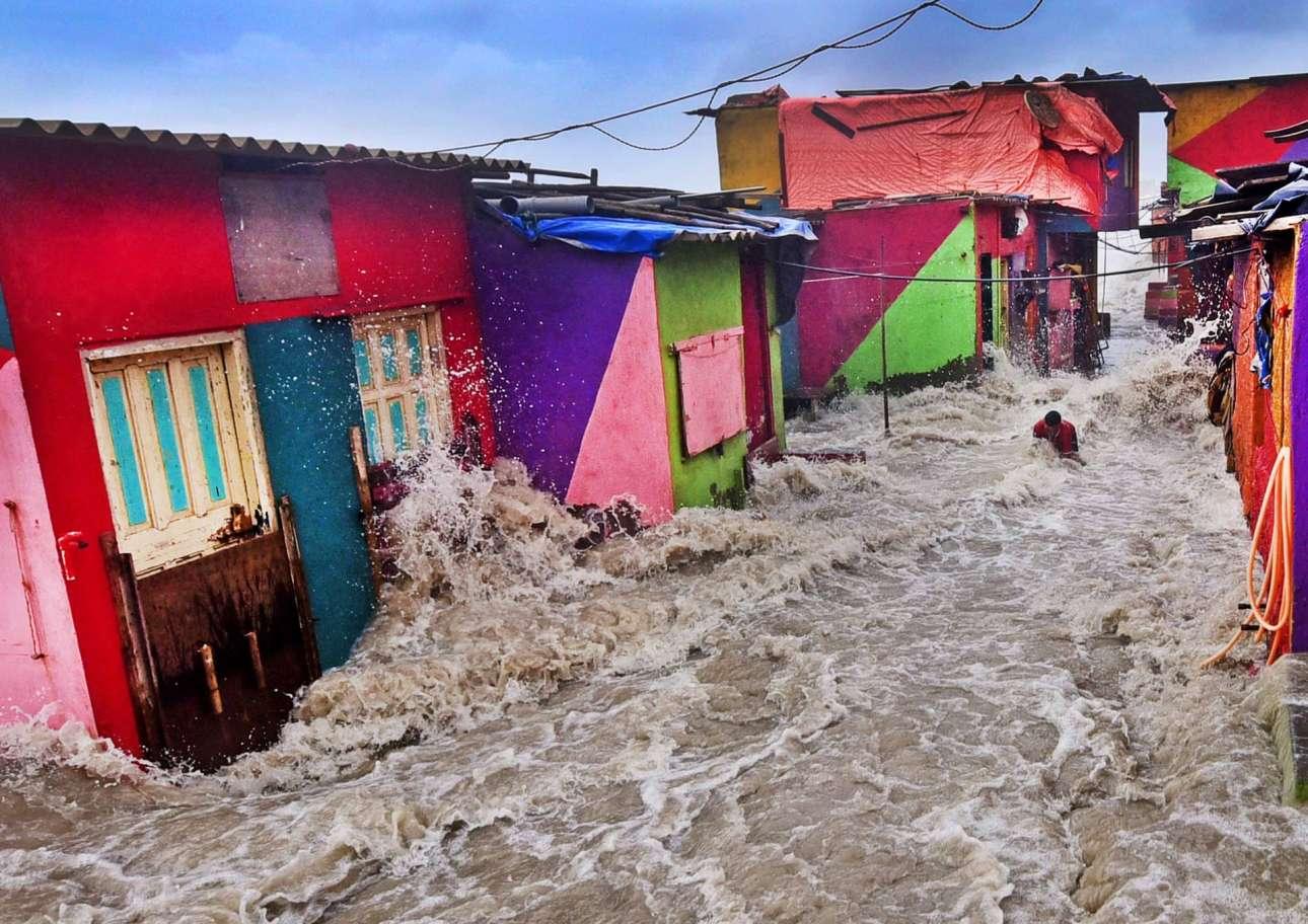 Φωτογράφος Περιβάλλοντος της Χρονιάς. Ορμητικό, τεράστιο κύμα παρασέρνει έναν ψαρά έξω από την καλύβα του στη Μουμπάι (Βομβάη) της Ινδίας. Η μεγαλούπολη αυτή κινδυνεύει από πλημμύρες ως αποτέλεσμα της κλιματικής αλλαγής, καθώς η θερμοκρασία στην ξηρά και στο νερό έχουν αυξηθεί προκαλώντας αντίστοιχα και την άνοδο στο επίπεδο της θάλασσας