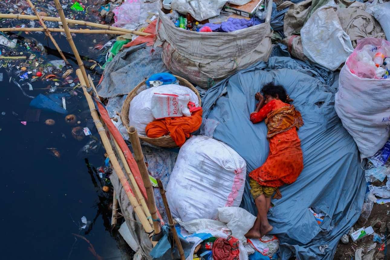 Στη Ντάκα πάλι, μία γυναίκα κοιμάται στην γεμάτη σκουπίδια όχθη ενός ποταμού