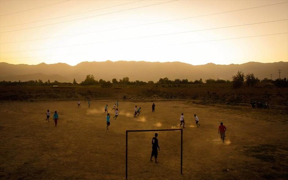 Μια παρέα παιδιών παίζει ποδόσφαιρο σε χωριό λίγο έξω από την Καμπούλ του Αφγανιστάν