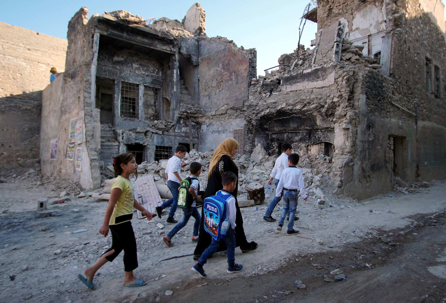 Κανονικότητα αλά Ιράκ: τριγύρω χαλάσματα, αλλά η μάνα συνοδεύει τα παιδιά της και τα γειτονόπουλα στο σχολείο τους, κάπου στη Μοσούλη