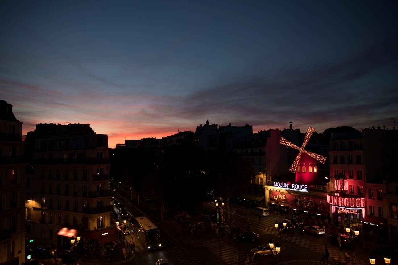 Ο ήλιος δύει στο Παρίσι, πάνω από τον διάσημο «Κόκκινο Μύλο»
