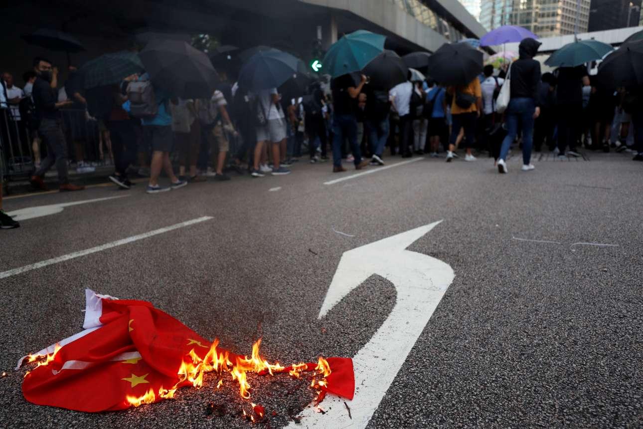 Ο φακός θέλησε να δείξει ότι νεαροί στο Χονγκ Κονγκ έκαψαν την κινεζική σημαία και απομακρύνθηκαν ανενόχλητοι - άλλη μία απόδειξη ότι η Κίνα είναι μεν μονοκομματική, όχι όμως και κομμουνιστική χώρα...