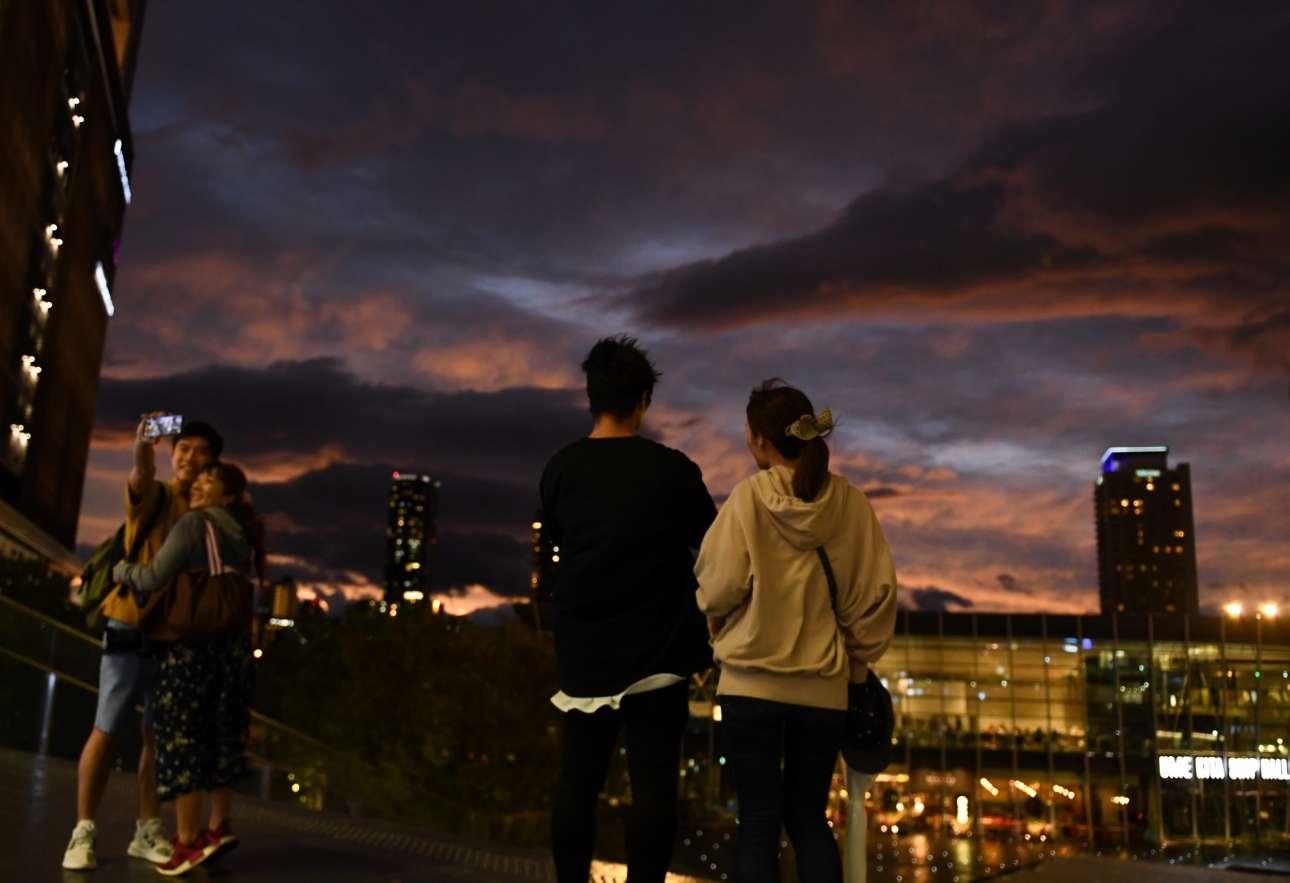 Ζευγαράκια βγάζουν σέλφι και ρεμβάζουν στην Οσάκα με φόντα τα βαριά σύννεφα του «Χαγκίμπις» που πλησιάζει