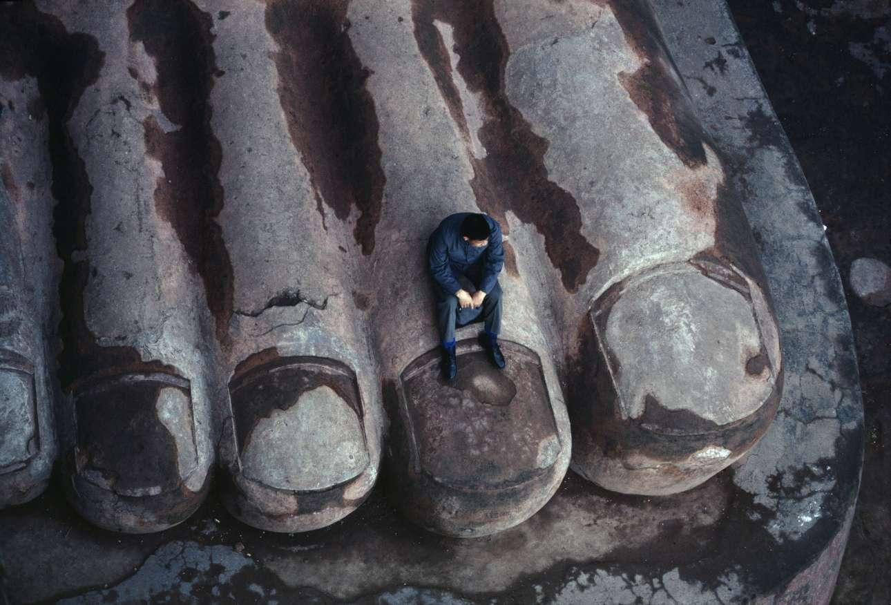 «Η φωτογραφία τραβήχτηκε το 1980. Δείχνει το πόδι του γιγαντιαίου αγάλματος του Βούδα του Λεσάν, το οποίο χτίστηκε μεταξύ 713 και 803 μ.Χ. Στα 71 μέτρα, είναι ο ψηλότερος βούδας του κόσμου. Από το 1996 έχει χαρακτηριστεί Μνημείο Παγκόσμιας Κληρονομιάς της UNESCO. Σήμερα απαγορεύεται να κάθεσαι στα πόδια του Βούδα ... »
