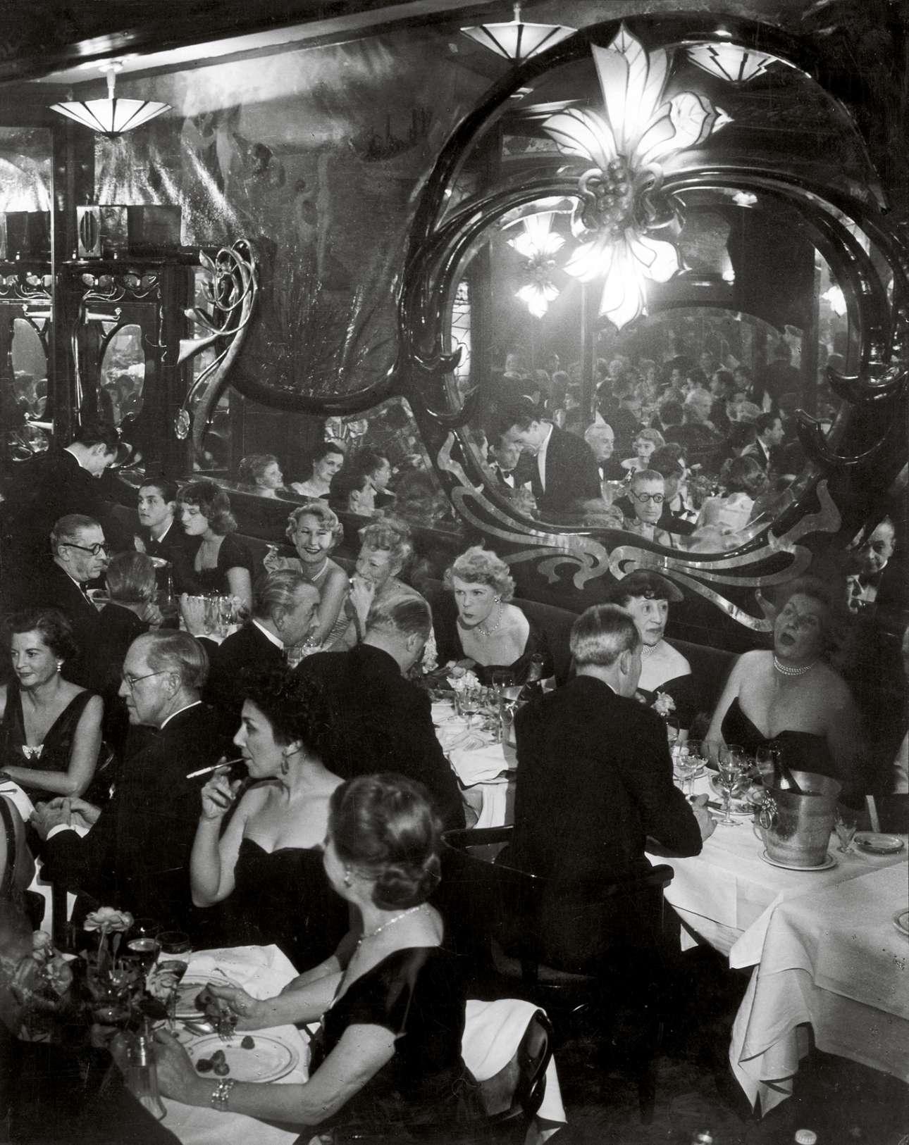 Κοσμικό γκαλά στο εστιατόριο Maxim's, τον Μάιο του 1949. Το παγκοσμίου φήμης εστιατόριο ήταν στέκι των Ναζί αξιωματικών κατά τη διάρκεια του Β' Παγκοσμίου Πολέμου, ύστερα το έκλεισε η Γαλλική Αντίσταση και άνοιξε ξανά στο τέλος της δεκαετίας του 1940 φιλοξενώντας διασήμους όπως η Μαρία Κάλλας και ο Αριστοτέλης Ωνάσης