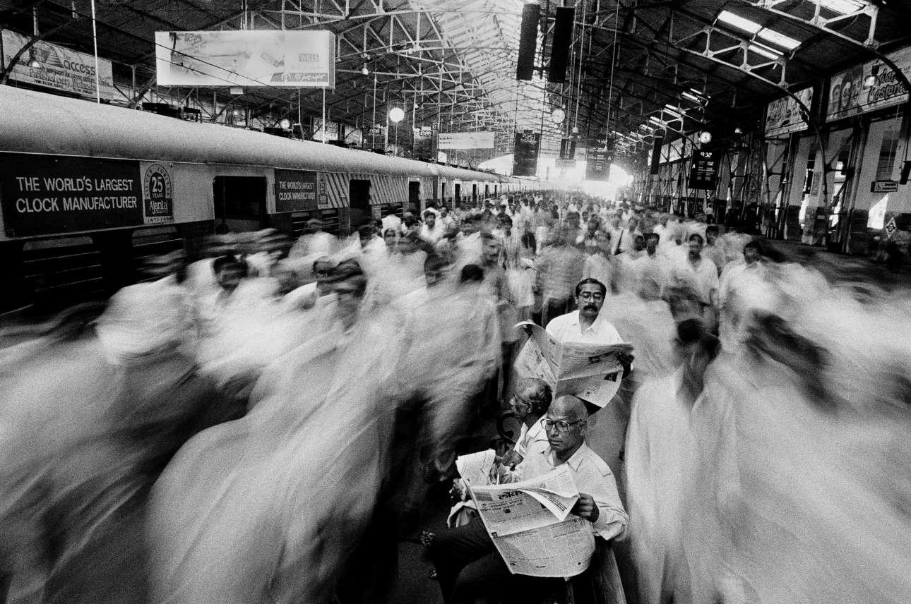 Εργαζόμενοι που πηγαίνουν στη δουλειά τους στο σταθμό Τσερτσγκέιτ του Μουμπάι, Ινδία, 1995. Ο φωτογράφος είχε ακούσει για τον κόσμο που πλημμυρίζει τις πλατφόρμες όταν φτάνει το τρένο και έτσι αποφασίσε να επισκεφτεί τον σταθμό Τσερτσγκέιτ στην πιο πολυσύχναστη ώρα, στις 8 το πρωί. «Στάθηκα εκεί με δέος και έκπληξη, με μία απίστευτη έντονη αίσθηση του κατακλυσμού από κόσμο. Χρειάστηκε λιγότερο από ένα λεπτό για να εξαφανιστούν χιλιάδες επιβάτες. Η πλατφόρμα ήταν άδεια και πάλι μέχρι 3 ή 4 λεπτά αργότερα, όπου έφτασαν περισσότερες αμαξοστοιχίες για να φέρουν μια ακόμη λαοθάλασσα. Περισσότερο από το πλήθος, ήθελα να αιχαμαλωτίσω τα τόσα πολλά ανθρώπινα σώματα που χάνονται το ένα μέσα στο άλλο και εξαφανίζονται σε μια τρελή βιασύνη για να φτάσουν στις δουλειές τους. Εστησα τη μηχανή μου ψηλά με χρόνο έκθεσης 1.8 δευτερόλεπτα και κατέγραψα την πλημμύρα. Εκείνοι όμως που καθόντουσαν και διάβαζαν εφημερίδα ή περίμενα κάποιον έμειναν ακίνητοι. Αυτήν την έκφραση τη συναντάς οποιαδήποτε στιγμή της ημέρας στις περισσότερες μητροπολιτικές πόλεις της Ινδίας»