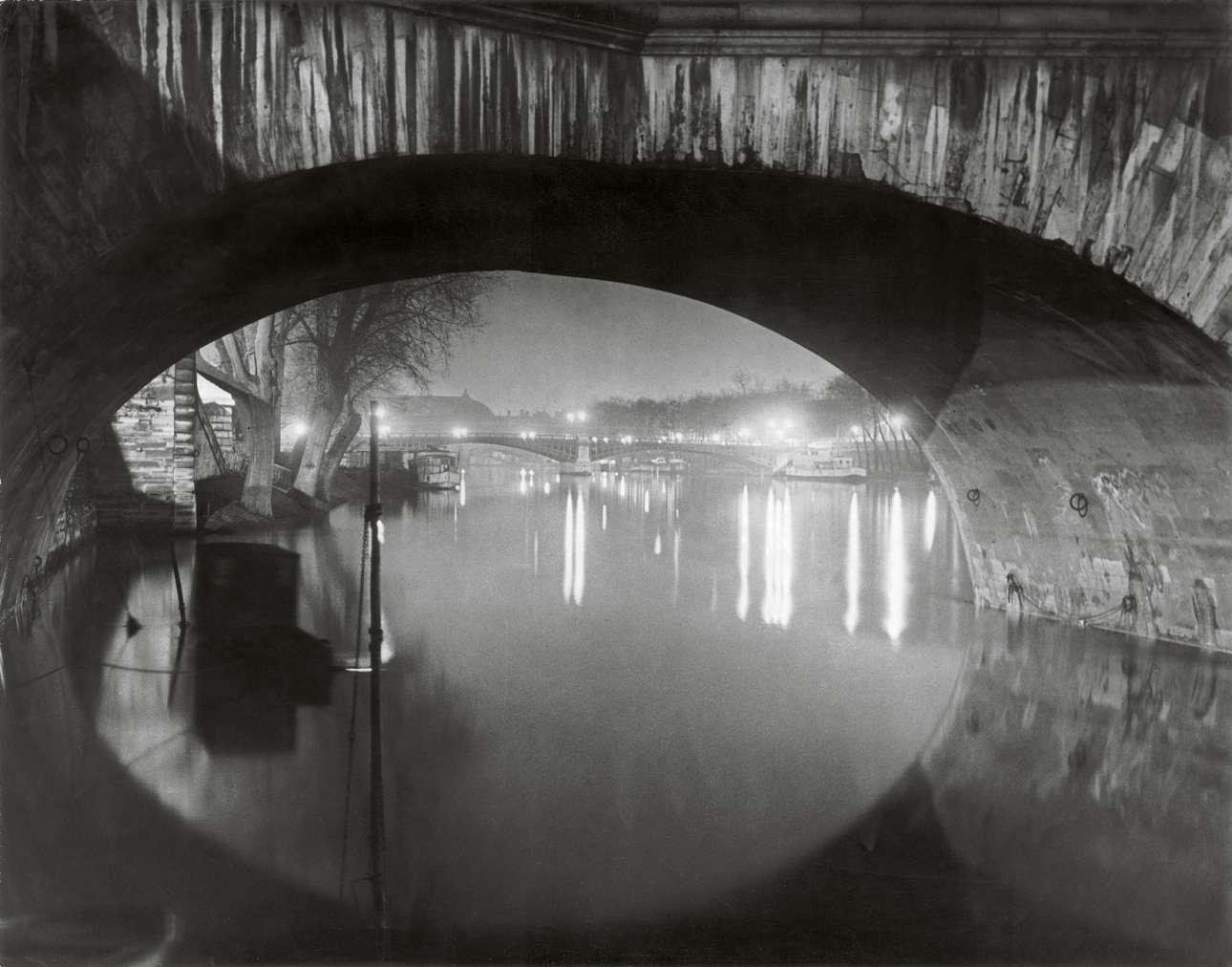 Ενα διαφορετικό καρέ νυχτερινής ζωής... η θέα από το γεφύρι του Pont Royal προς εκείνο του Pont Solferino στο Σηκουάνα, το 1933. Σύμφωνα με τον Μπρασάι «η νύχτα ποτέ δεν αποκαλύπτει καταστάσεις, απλώς τις υπονοεί».