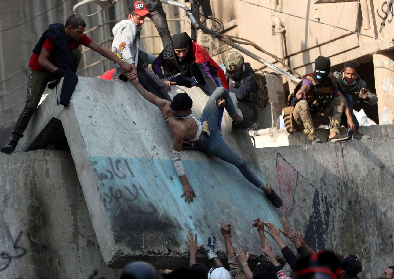 Βαγδάτη, Ιράκ: επιχείρηση απομάκρυνσης τραυματία από τον χώρο των επεισοδίων που έγιναν κατά τη διάρκεια αντικυβερνητικής διαδήλωσης
