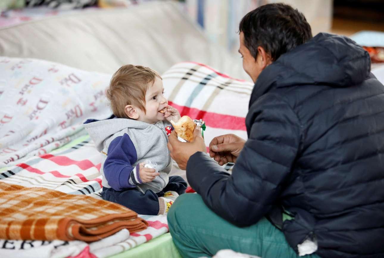Δυρράχιο, Αλβανία: το τάισμα του παιδιού δίνει χαρά και στον πατέρα – ένα χαρούμενο διάλειμμα μέσα στη σκηνή της σεισμόπληκτης οικογένειας