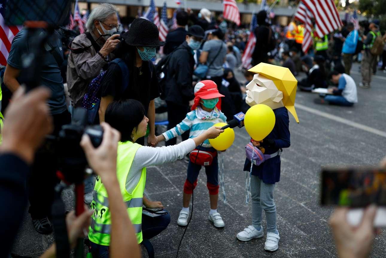 Και κάπου όπου ο Ντόναλντ Τραμπ είναι ήρωας. Στο Χονγκ Κονγκ, στην κυριακάτικη πορεία «Ευγνωμοσύνης προς τις ΗΠΑ», ένα παιδί φορά τη μάσκα του αμερικανού προέδρου, του μόνου που ορθώνει το ανάστημά του απέναντι στην ισχύ της Λαϊκής Κίνας