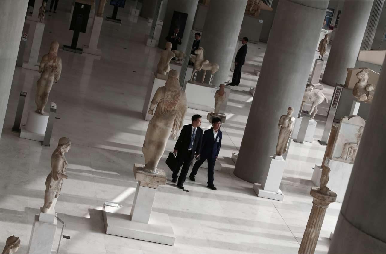 Μέλη της συνοδείας παρατηρούν τα αγάλματα σε μία από τις αίθουσες του Μουσείου