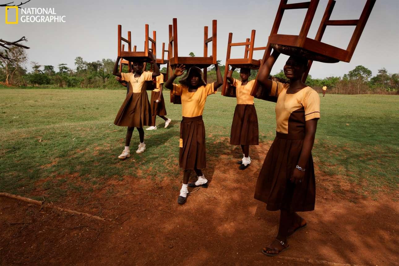 Μαθήτριες στη Γκάνα βοηθούν στις προετοιμασίες για τα εγκαίνια της Μαιευτικής Κλινικής Maranatha κουβαλώντας καρέκλες για την τελετή