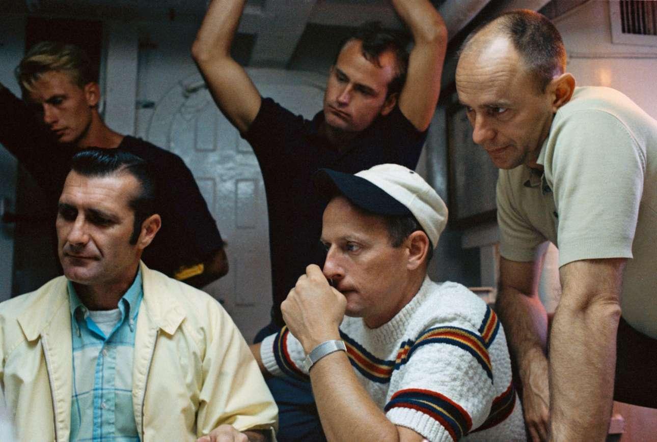 Τα τρία μέλη του πληρώματος του Apollo 12 ενημερώνονται στο κέντρο της NASA, ώστε να είναι καλά προετοιμασμένοι για το τελευταίο «βήμα» της αποστολής τους, την προσθαλάσσωση στον Κόλπο του Μεξικού. Από τα αριστερά προς τα δεξιά: ο Ρίτσαρντ Γκόρντον, ο Τσαρλς Κόνραντ, ο Αλαν Μπιν και οι δύο εκπαιδευτές που φαίνονται όρθιοι από πίσω τους