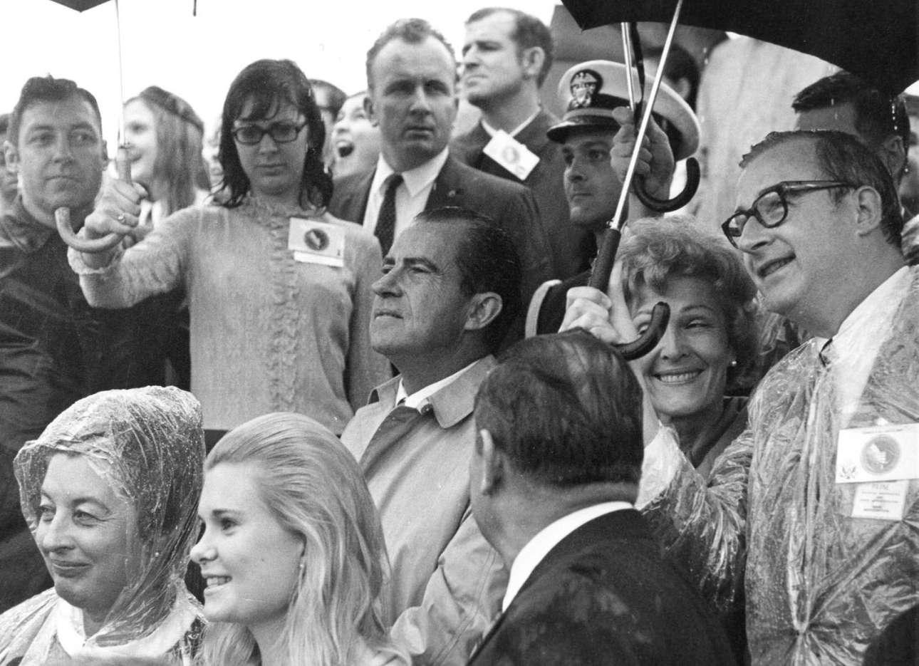 O πρόεδρος Νίξον παρακολουθεί ενώ ο διευθυντής της NASA Τόμας Πέιν προστατεύει από τη βροχή με την ομπρέλα του την πρώτη κυρία Πατ Νίξον και την κόρη της Τρίσια (η ξανθιά μπροστά), που παρακολουθούν τις δραστηριότητες προεκτόξευσης του Apollo 12