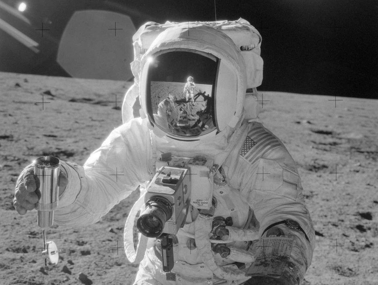 Ο Αλαν Μπιν κράτα ένα ειδικό δοχείο για τη συλλογή περιβαλλοντικών δειγμάτων από τη Σελήνη, στο οποίο έχει συγκεντρώσει χώμα. Ο Τσαρλς Κόνραντ που τον βγάζει φωτογραφία, διακρίνεται στον αντικατοπτρισμό του κράνους του