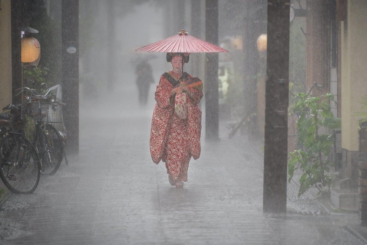 Μία ασκούμενη γκέισα με κερωμένη, μεταξωτή ομπρέλα προσπαθεί να προστατευτεί από τη βροχή στο Κιότο της Ιαπωνίας