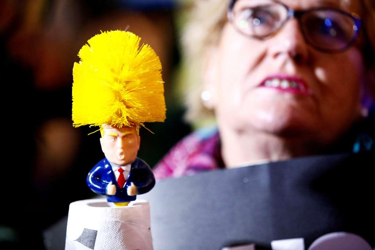 Το πορτοκαλί-κίτρινο μαλλί του Ντόναλντ Τραμπ μεταμορφωμένο σε σκουπάκι τουαλέτας στα χέρια διαδηλώτριας στο Λονδίνο