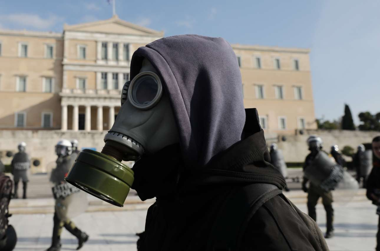 Μια άλλη πορεία, αυτή στην Αθήνα για τα 11 χρόνια από τη δολοφονία του Αλέξανδρου Γρηγορόπουλου: ενας διαδηλωτής με αντιασφυξιογόνο μάσκα μπροστά από αστυνομικούς