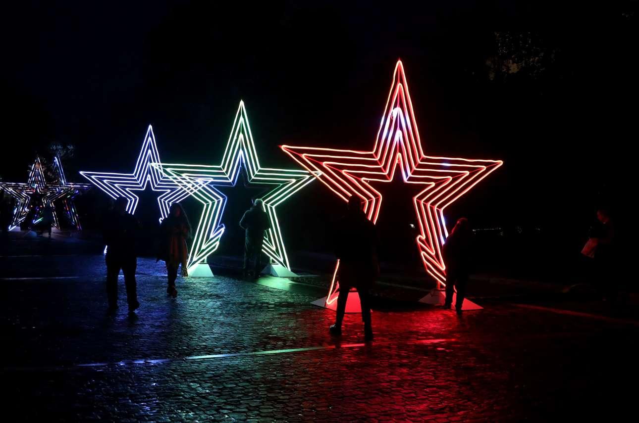 Αστέρια τεράστια, χρωματιστά, φυτεμένα στο πλακόστρωτο της Διονυσίου Αρεοπαγίτου λένε στους περαστικούς ότι οι μέρες είναι χρονιάρες και στην Αθήνα