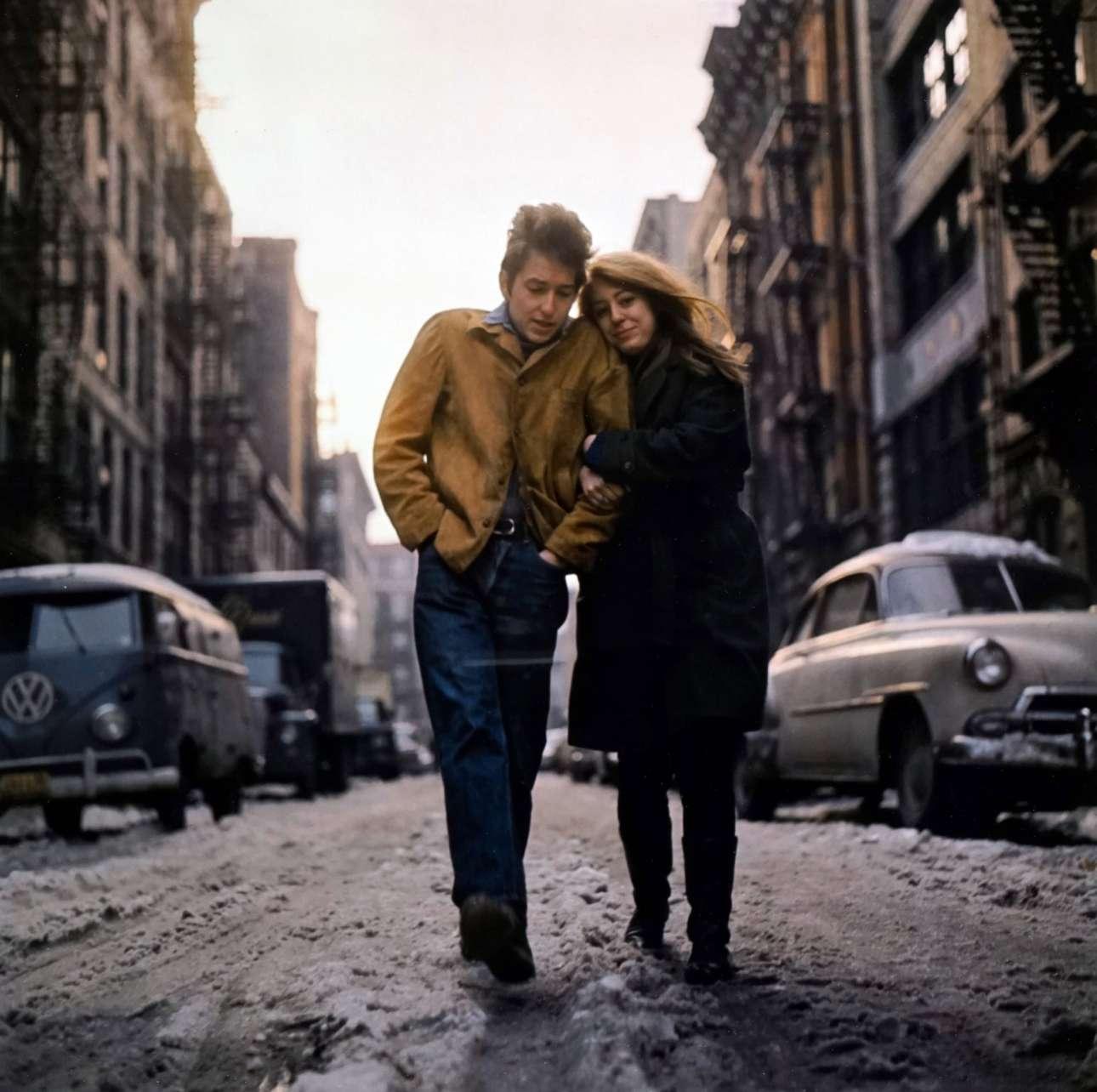Ο Μπόμπ Ντίλαν με την Σουζ, στη Νέα Υόρκη το 1966. «Λοιπόν, δεν μπορώ να σας πω γιατί το έκανα, αλλά είπα: 'απλά περπατήστε πάνω και κάτω στον δρόμο'. Ηταν αργά το απόγευμα - μπορείτε να δείτε ότι ο ήλιος ήταν χαμηλά πίσω τους. Πρέπει να ήταν αρκετά άβολα εκεί έξω στο λασπωμένο χιόνι» διηγείται ο φωτογράφος Ντον Χανστάιν