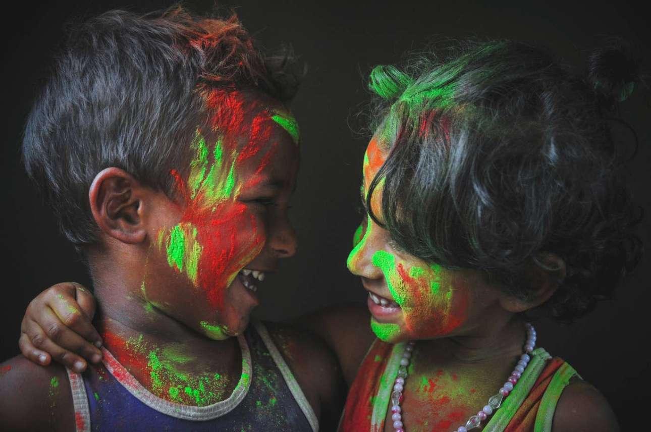 Δύο παιδιά γιορτάζουν το ινδουιστικό φεστιβάλ Χόλι. «Το Χόλι είναι το φεστιβάλ των χρωμάτων: είναι μια εποχή που οι φίλοι έρχονται κοντά και αφήνουν όλες τις διαφορές τους να πνιγούν στα χρώματα. Στο Μπαγκλαντές οι Ινδουιστές είναι μειονότητα, ωστόσο επειδή είναι μια χώρα πολυπολιτισμικής διασποράς, γιορτάζουν το Χόλι αγκαλιάζοντας τους μουσουλμάνους αδελφούς τους: είναι μια εποχή που όλες οι διαμάχες ξεχνιούνται κάτω από τις χιλιάδες χρωματιστές σκόνες»