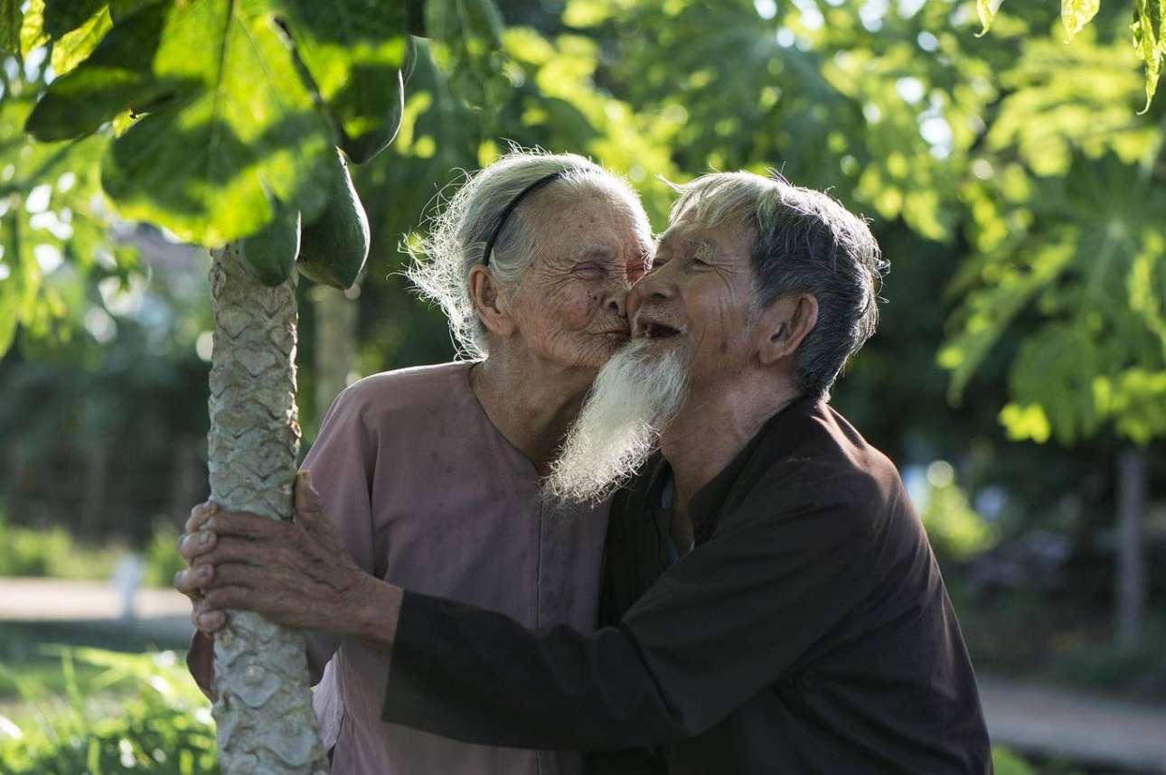 Το ζευγάρι της φωτογραφίας είναι γνωστό ως το πιο ευτυχισμένο ζευγάρι στο χωριό Χόι Αν του Βιετνάμ. «Είναι οι πιο ευτυχισμένοι άνθρωποι που έχω δει, είναι 95 ετών και αγαπούν ο ένας τον άλλο πολύ. Πάντα χαμογελούν, ίσως το χαμόγελο τους βοηθά να είναι πάντα μαζί και ευτυχισμένοι. Πολλοί τους βγάζουν φωτογραφία, αλλά δυστυχώς η γυναίκα πέθανε πριν από ένα χρόνο. Εκτοτε, κανείς δεν έχει έρθει να φωτογραφίσει πια εκείνον - είναι πολύ λυπημένος, αλλά τον επισκέπτομαι συχνά και τον απαθανατίζω στις στιγμές που την αναπολεί. Αν κερδίσω, θα χρησιμοποιήσω τα χρήματα για να του αγοράσω φάρμακα για να βελτιώσει την υγεία του, καθώς εύχομαι να ζήσει μέχρι τα 100 χρόνια», λέει ο φωτογράφος