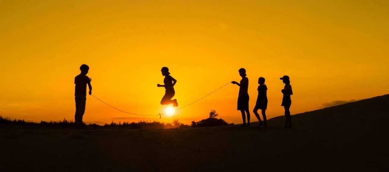Παιδιά κάνουν λάστιχο, καθώς ο ήλιος δύει στο Βιετνάμ