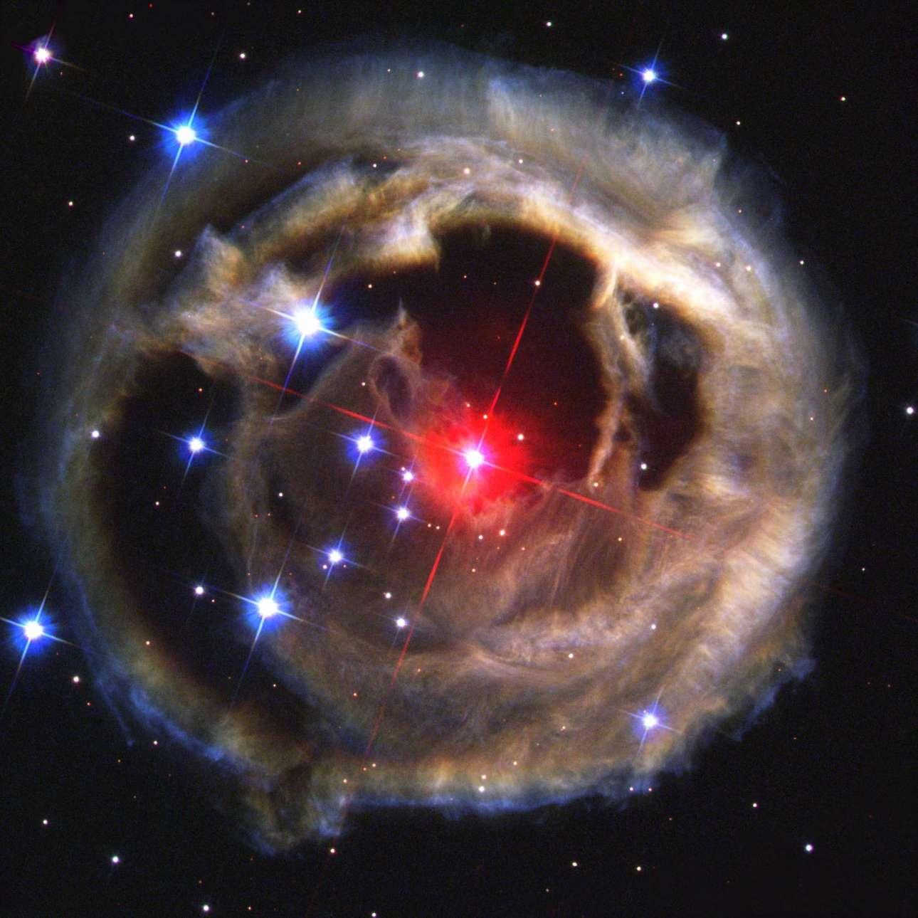 «To γιγάντιο φωτοστέφανo». Κολοσσιαίες ποσότητες κοσμικής ύλης στροβιλίζονται σε έκταση τρισεκατομμυρίων χλμ. στο Διάστημα δημιουργώντας ένα νεφέλωμα αερίων και σκόνης που μοιάζει με ένα υπέρλαμπρο φωτοστέφανο γύρω από το άστρο V838 Monocerotis. Το άστρο βρίσκεται σε απόσταση 20 χιλιάδων ετών φωτός από εμάς στον αστερισμό του Μονόκερου. Πριν από 18 έτη οι αστρονόμοι εντόπισαν ένα εντυπωσιακό κοσμικό φαινόμενο στην συγκεκριμένη περιοχή. Το V838 Monocerotis έγινε ξαφνικά ένα εκατομμύριο φορές πιο λαμπρό από τον Ήλιο και για λίγο καιρό ήταν το πιο φωτεινό αντικείμενο στον γαλαξία μας. Αρχικά οι επιστήμονες θεώρησαν ότι είχαμε να κάνουμε με μια συνηθισμένη έκρηξη σουπερνόβα η οποία κατέστρεψε το άστρο. Από τις παρατηρήσεις διαπιστώθηκε ότι εδώ δεν έχουμε να κάνουμε μια έκρηξη αλλά με διαδοχικές  εκρήξεις γεγονός που δεν μπορούν να εξηγήσουν οι ειδικοί. Μια εκτίμηση είναι ότι οι διαδοχικές εκρήξεις είναι αποτέλεσμα της καταστροφής των πλανητών που είχαν σχηματιστεί γύρω από το συγκεκριμένο άστρο οι οποίοι καθώς έφτανε σε εκείνους το «κοσμικό τσουνάμι» της αστρικής έκρηξης καταστρέφονταν και αυτοί. Μια δεύτερη εκτίμηση είναι το V838 Monocerotis ήταν δυαδικό σύστημα και οι εκρήξεις είναι το αποτέλεσμα της συγχώνευσης των δύο άστρων. Δύο χρόνια μετά τον εντοπισμό του φαινομένου το Hubble κατέγραψε αυτή την εικόνα.