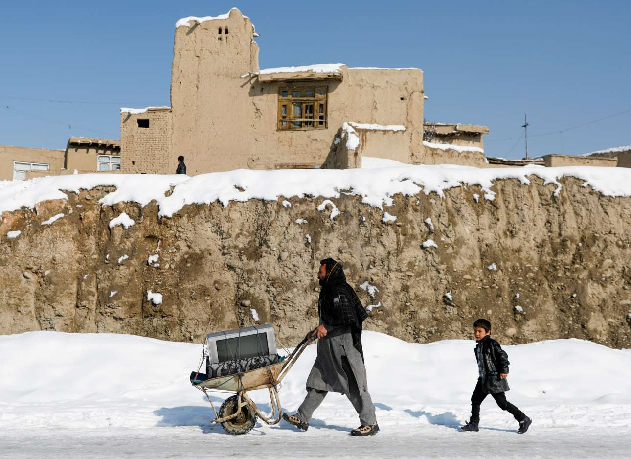 Μεταφορά τηλεόρασης με ένα καροτσάκι της οικοδομής στη χιονισμένη Καμπούλ