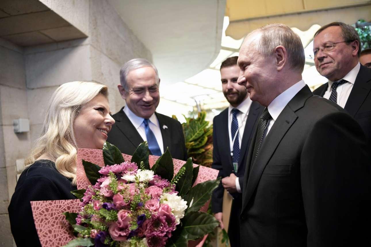 Ο Βλαντίμιρ Πούτιν έχει μάλλον ευχάριστη συζήτηση με την κυρία Νετανιάχου, τη Σάρα, ενώ ο «Μπίμπι» τους παρακολουθεί χαμογελαστός