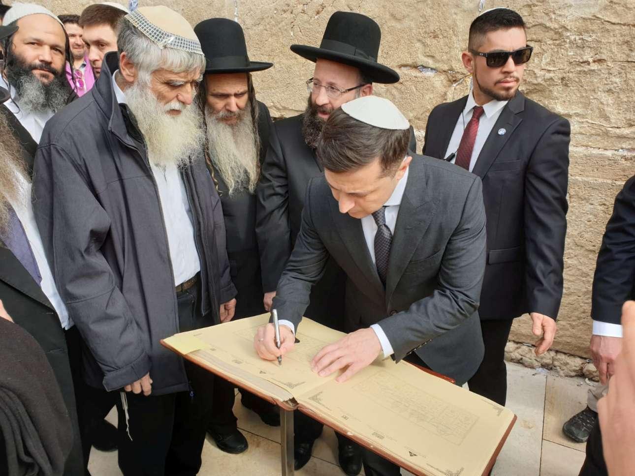 Ο πρόεδρος της Ουκρανίας Βολοντίμιρ Ζελένσκι, φορώντας κιπά, υπογράφει σε βιβλίο επισκεπτών και ετοιμάζεται να παρακολουθήσει μια τελετή στην παλιά πόλη της Ιερουσαλήμ
