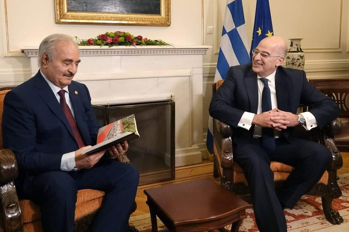 Στιγμιότυπο από την αθηναϊκή συνάντηση του λίβυου στρατηγού Χαλίφα Χαφτάρ με τον υπ. Εξωτερικών Νίκο Δένδια, λίγο πριν από τη διάσκεψη του Βερολίνου. Το δώρο βιβλίο-λεύκωμα που περιεργάζεται ο μουσαφίρης αφορά του ευζώνους της προεδρικής φρουράς [