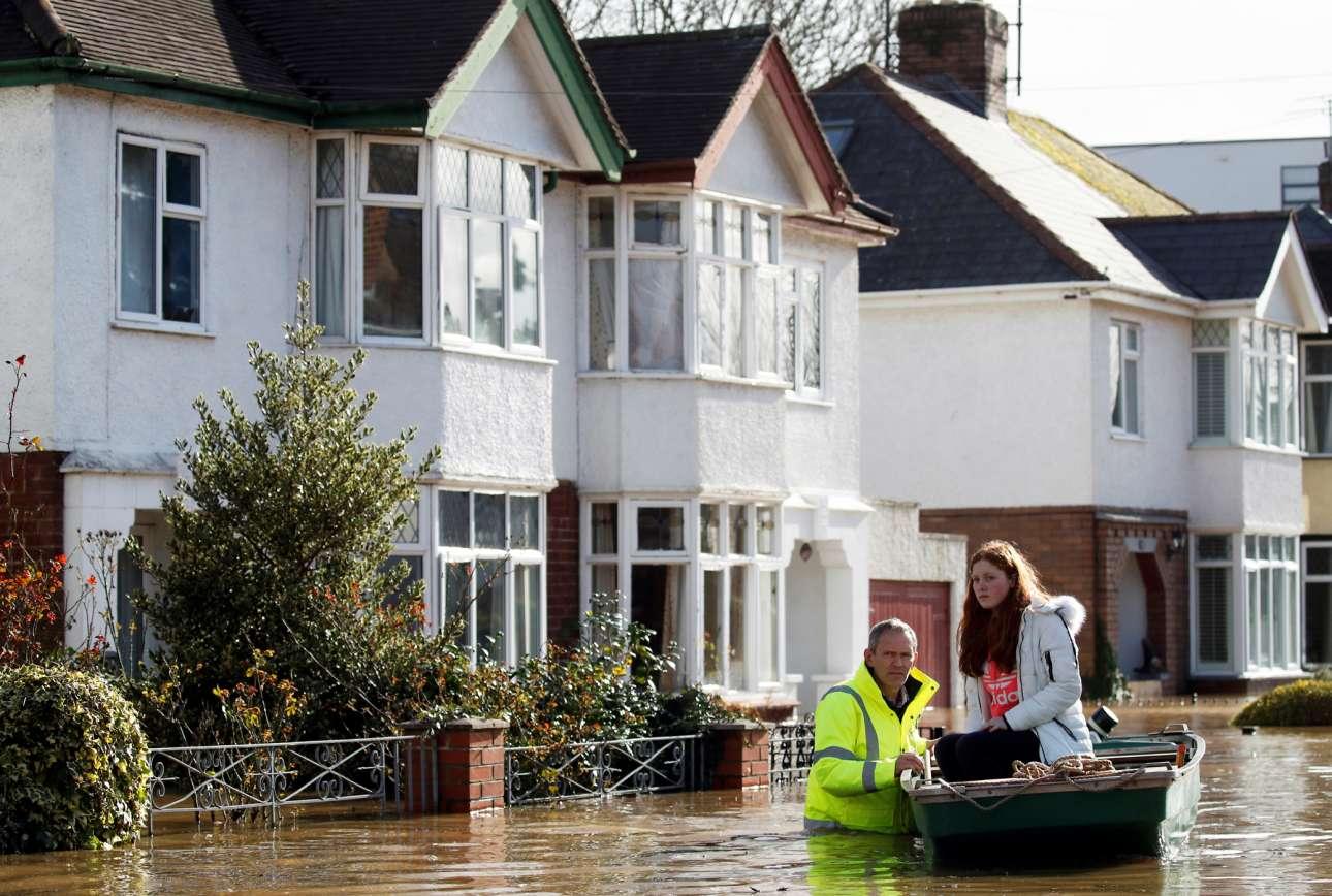 Βρετανία. Διασώστης απομακρύνει με βάρκα μία κοπέλα από τη γειτονιά που πλημμύρισε όταν πέρασε από εκεί η καταιγίδα «Ντένις»