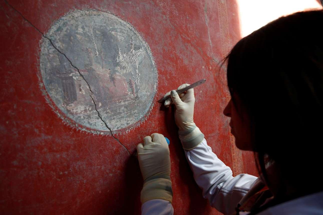 Μία ειδικός του ιταλικού υπουργείου Πολιτισμού συντηρεί τοιχογραφία στο Σπίτι των Εραστών, μία από τις τρεις βίλες που ανοίγουν ξανά για το κοινό, 40 χρόνια μετά το κλείσιμό τους