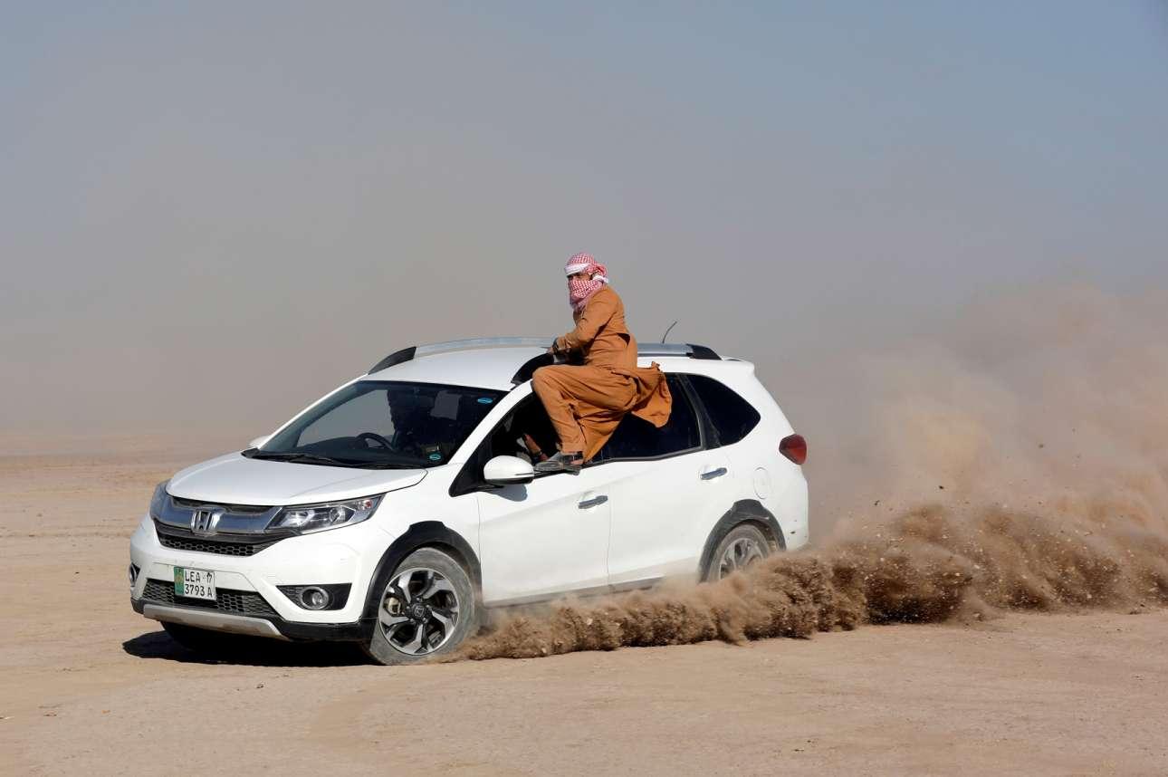 Ερημος Πακιστάν. Ενας λάτρης της αυτοκίνησης ισορροπεί σε παράθυρο οχήματος εν κινήσει, σε μια ριψοκίνδυνη επίδειξη, κατά το 15ο Cholistan Desert Rally 2020