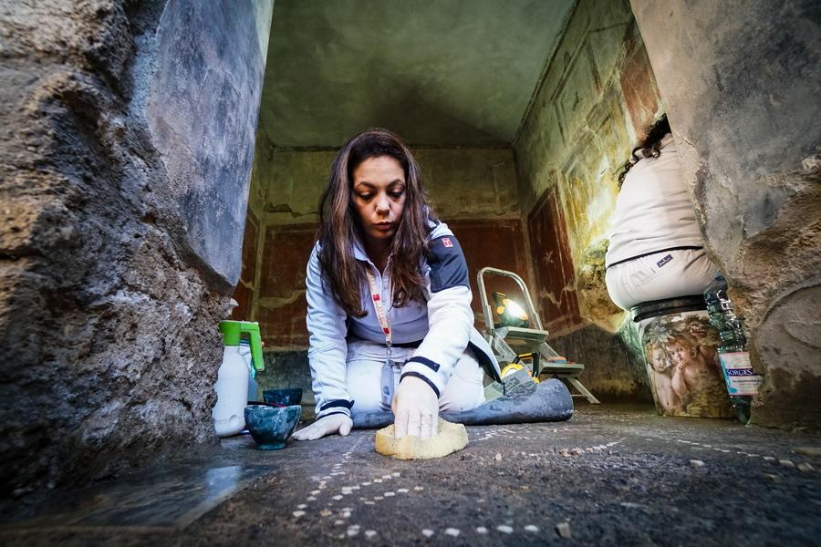 Συντηρήτρια του ιταλικού υπουργείου Πολιτισμού φροντίζει το μωσαϊκό σε πάτωμα στο Σπίτι των Εραστών