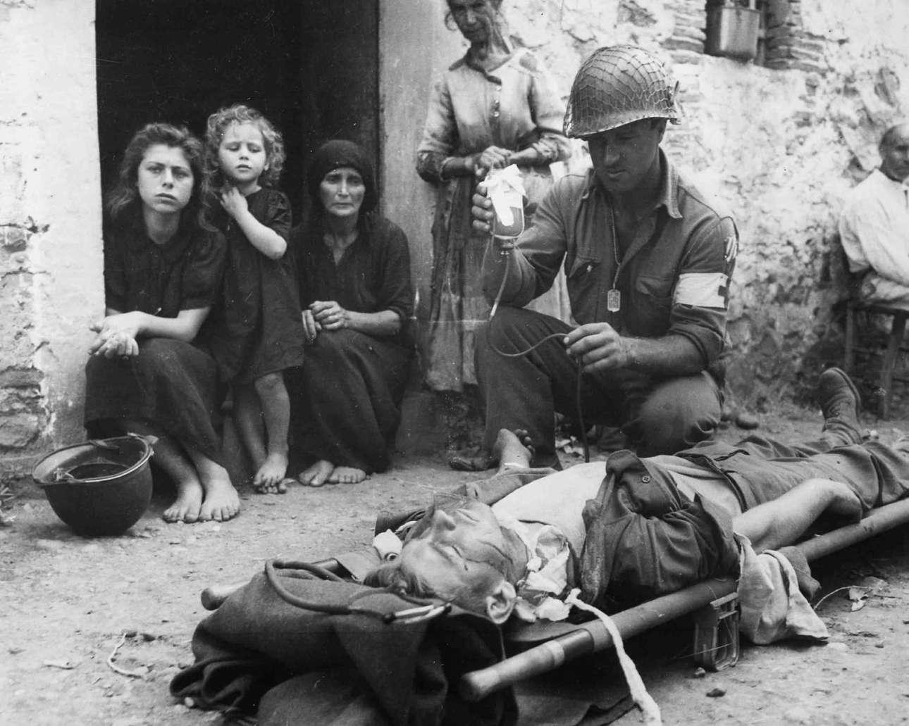 8 Αυγούστου 1943, Σικελία: αμερικανός στρατιώτης του Υγειονομικού μεταφέρει συνάδελφό του που τραυματίστηκε από θραύσματα βόμβας και του μεταγγίζεται αίμα